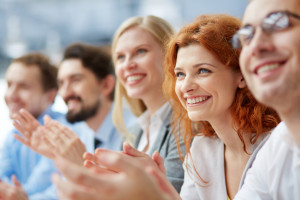 Photo of happy business people applauding at conference, focus on smiling female