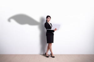 Superhero business woman using laptop computer with white wall background, great for your design or text, asian